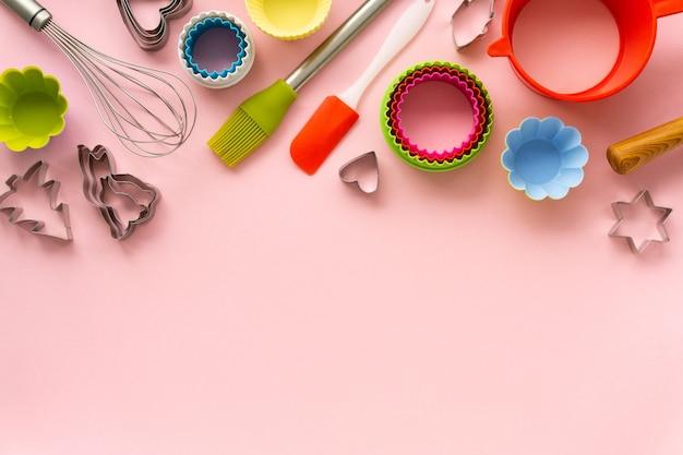 Plat leggen van verschillende bakgerei op roze achtergrond. ruimte voor tekst.