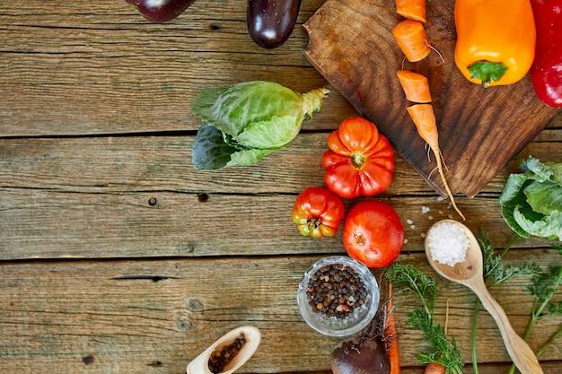 Plat leggen van verschillende biologische groenteningrediënten en pittig op houten ondergrond, lokaal eten, vegetarisch en veganistisch eten, dieetlenteconcept, bovenaanzicht, kopieerruimte.
