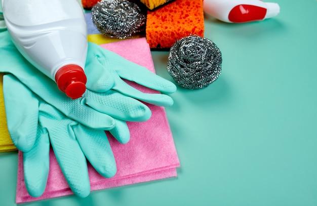 Plat leggen van verschillende huisreinigingsproduct op blauwe tafel, reinigingsset voor verschillende oppervlakken, wasmiddelen serviceconcept, bovenaanzicht.