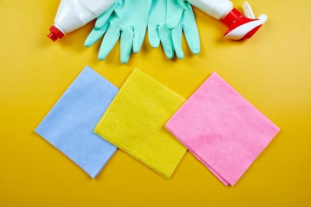Plat leggen van verschillende huisreinigingsproduct op gele tafel, reinigingsset voor verschillende oppervlakken, wasmiddelen serviceconcept, bovenaanzicht.