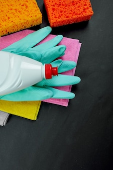 Plat leggen van verschillende huisreinigingsproduct op zwarte tafel, reinigingsset voor verschillende oppervlakken, wasmiddelen serviceconcept, bovenaanzicht.
