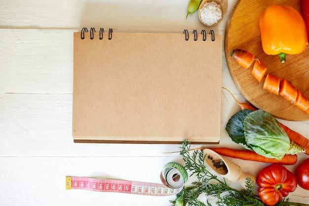Plat leggen van verschillende ingrediënten van biologische groenten en meetlint op houten oppervlak