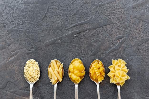 Plat leggen van verschillende pasta in lepels met kopie ruimte