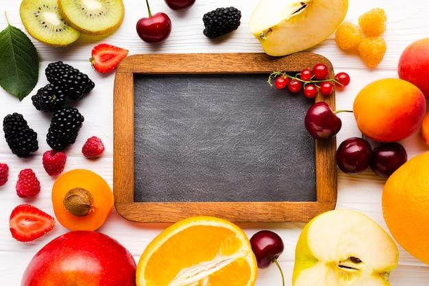 Plat leggen van verse bessen en fruit met schoolbord