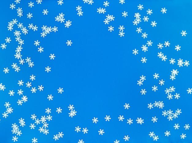 Plat leggen van verspreide witte sneeuwvlokken op blauw