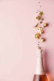 Plat leggen van viering. champagnefles en gouden decoratie op roze