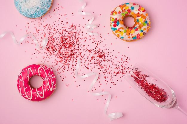 Plat leggen van viering. champagneglas met kleurrijke feestwimpels en heerlijke donuts op roze achtergrond.