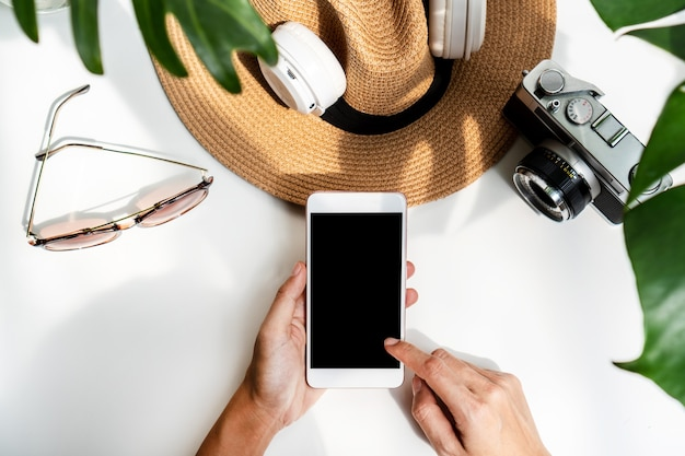 Plat leggen van vrouw handen met behulp van mobiele telefoon met zomer items op wit bureau.