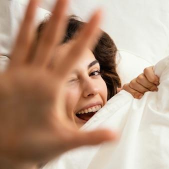 Plat leggen van vrouw verstopt onder de lakens thuis