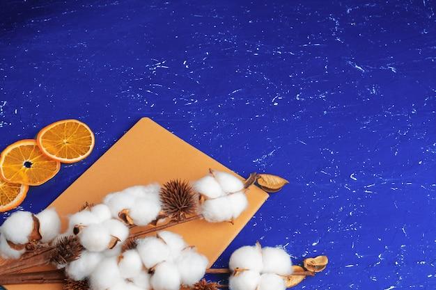 Plat leggen van vrouwelijke blauwe achtergrond met tak van kunstmatige katoenen bloem