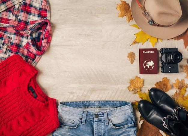 Plat leggen van vrouwenstijl en accessoires, rode gebreide trui, geruit overhemd, spijkerbroek, zwarte leren laarzen, hoed, herfstmodetrend, uitzicht van bovenaf, vintage fotocamera, paspoort