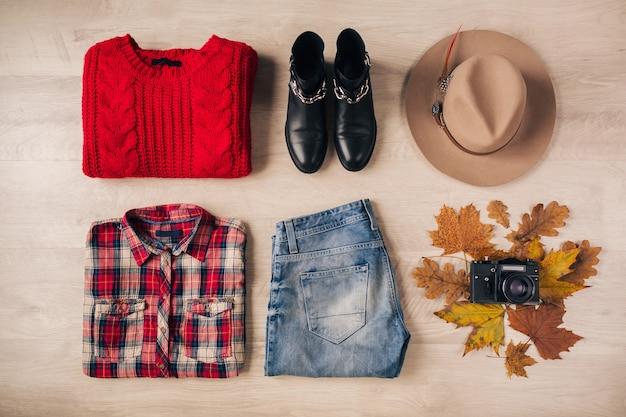 Plat leggen van vrouwenstijl en accessoires, rode gebreide trui, geruit overhemd, spijkerbroek, zwarte leren laarzen, hoed, herfstmodetrend, uitzicht van bovenaf, vintage fotocamera, reizigersoutfit