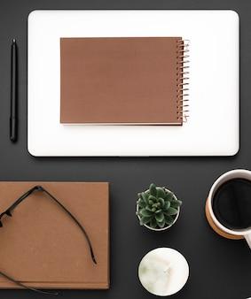 Plat leggen van werkstation met laptop en bril bovenop agenda