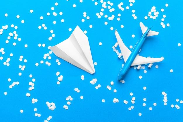Plat leggen van wit papier vliegtuig en blanco papier op pastel blauwe kleur