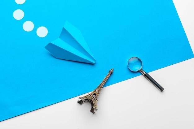 Plat leggen van wit papier vliegtuig en blanco papier op pastelblauw