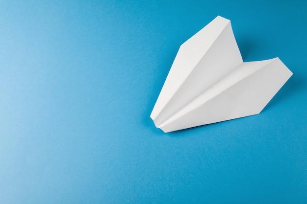 Plat leggen van wit papier vliegtuig op pastel blauwe kleur