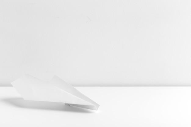 Plat leggen van wit papier vliegtuig op witte kleur achtergrond
