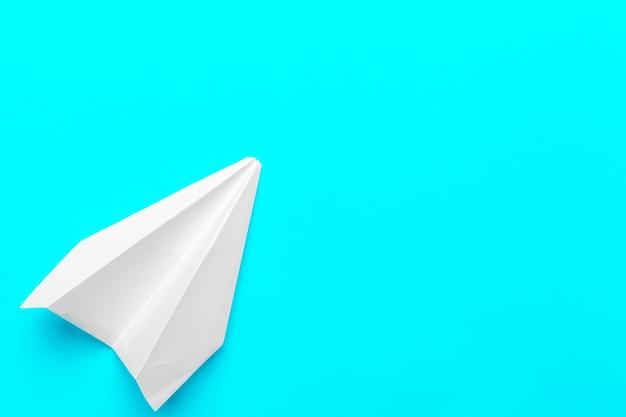 Plat leggen van witboek vliegtuig en blanco papier op pastel blauwe kleur achtergrond