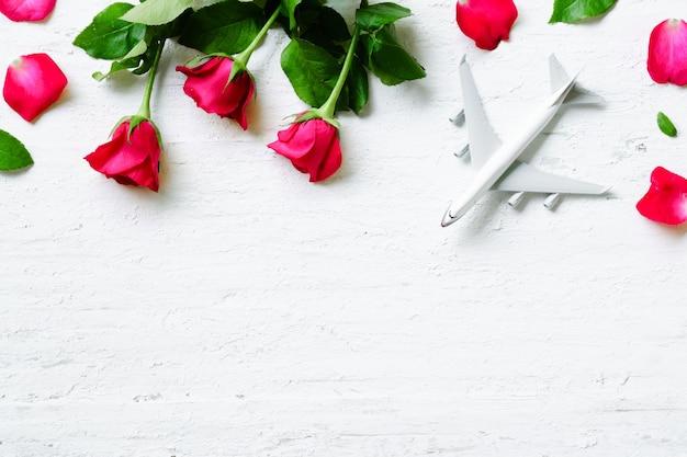 Plat leggen van witte lege model van passagiersvliegtuig met rozen