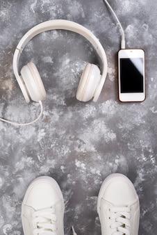 Plat leggen van witte sneakers op stenen achtergrond met telefoon en koptelefoon.