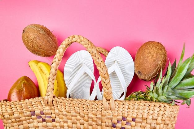 Plat leggen van zomer witte slippers rieten bamboe tas en vers exotisch fruit