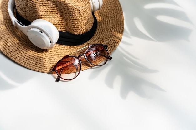 Plat leggen van zonnebril, strooien hoed en hoofdtelefoon met groene tropische bladschaduw op wit bureau