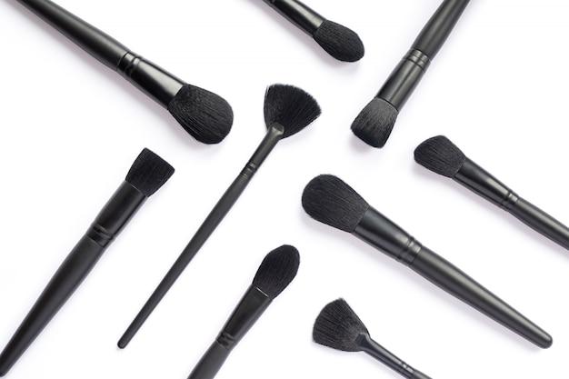 Plat leggen van zwarte make-up borstels collectie geïsoleerd op witte ruimte