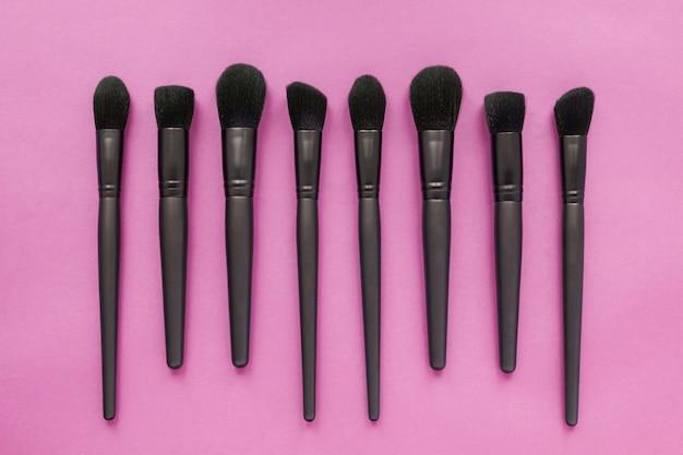 Plat leggen van zwarte make-upborstels op roze ruimte. bovenaanzicht van make-up borstels set