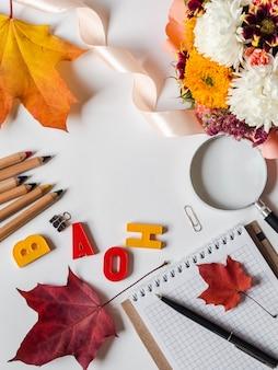 Plat leggen voor lerarendag van verschillende schoolattributen en een boeket met verschillende herfstbloemen