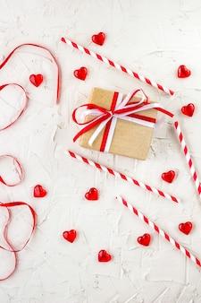 Plat leggen voor valentijnsdag met rode harten, kaarsen, confetti op witte achtergrond