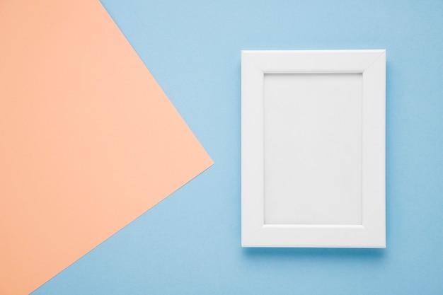Plat leggen wit frame op lichtblauwe en roze achtergrond