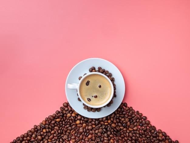 Plat leggen. witte ceramische kop met aromatische koffie op een heuvel van koffiebonen op een roze achtergrond.