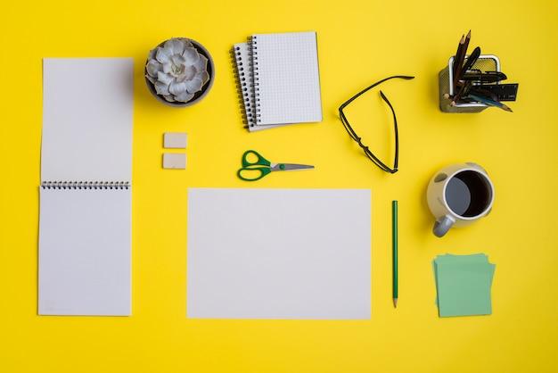 Plat leggen zakelijke werkplek met kantoorbenodigdheden en koffie op gele achtergrond