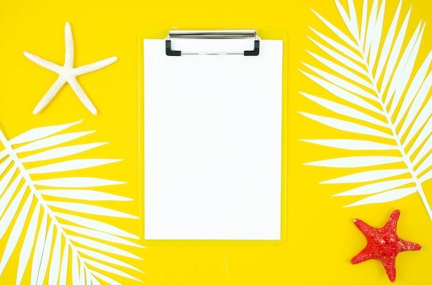 Plat leggen zomer klembord met palmbladeren en zeesterren op gele achtergrond