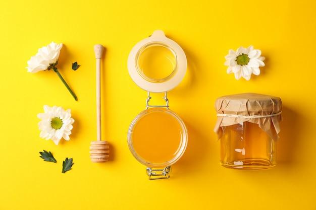 Plat liggen. potten met honing, beer en kamille op gele achtergrond, kopie ruimte