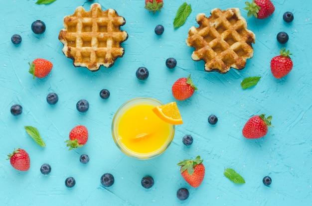 Plat liggen. wafels, sinaasappelsap, rode bessen en muntblaadjes op blauw oppervlak