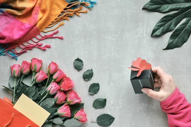 Plat liggend, arrangement met bos roze bloemen en exotische plant blad. hand die kleine giftdoos met harten op bovenkant houdt. bovenaanzicht op lichte steen. valentijnsdag, verjaardag of moederdag concept.