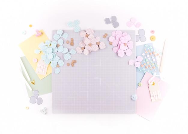 Plat liggend, bovenaanzicht ambachtelijk tafelbureau. werkruimte met mat voor snijden, schaar, cardstock, papier, potloden op witte achtergrond. maak een bloemenkransdecor.