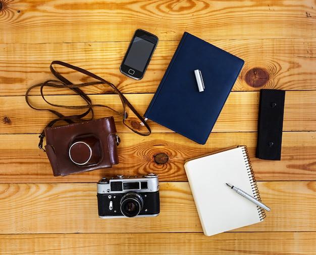 Plat liggende, bovenaanzicht kantoor tafel bureau. bureauwerkruimte met retro camera, agenda, pen, geval op houten.