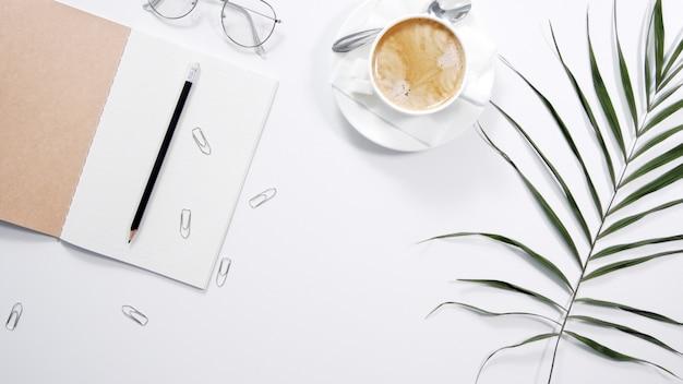 Plat liggende, bovenaanzicht kantoor tafel bureau. werkruimte met leeg klembord, kantoorbenodigdheden, potlood, groen blad en koffie