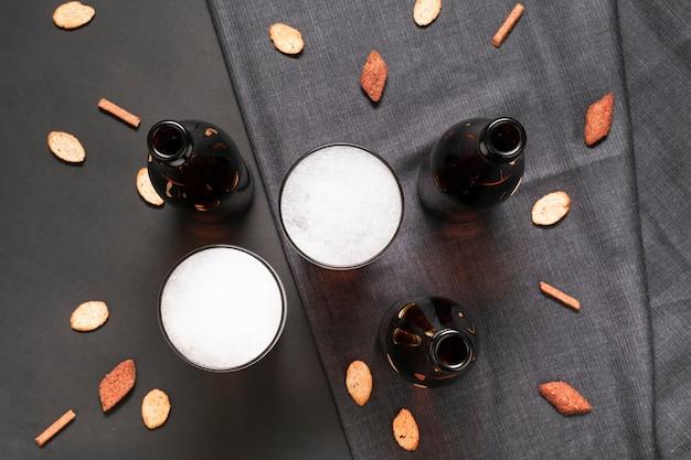 Plat liggende flessen en glazen bier met snacks