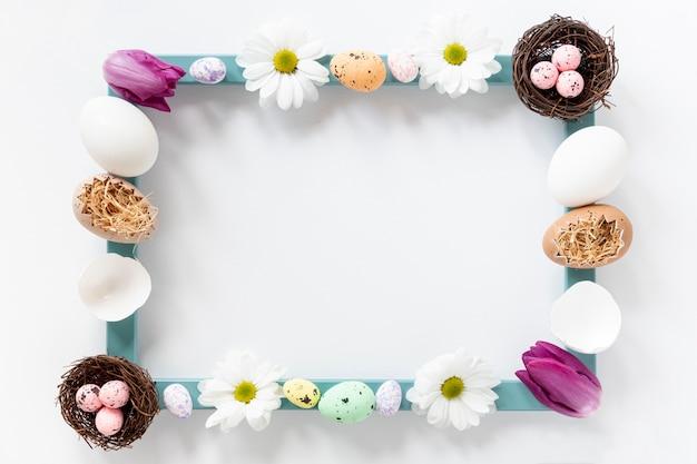 Plat liggende frame gemaakt van bloemen en eieren