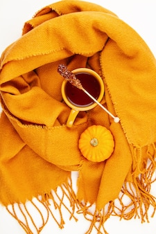 Plat liggende herfstcompositie met kopje thee en een warme wollen sjaal