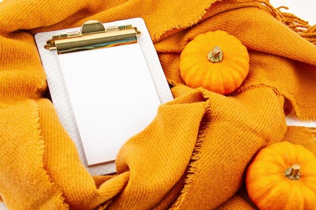 Plat liggende herfstcompositie met notitieblok en een warme wollen sjaal