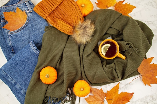 Plat liggende herfstsamenstelling met herfstbladeren, pompoenen, warme kop thee en een warme wollen sjaal en muts