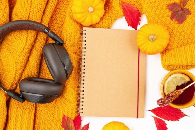 Plat liggende herfstsamenstelling met herfstbladeren, warme kop thee en een warme wollen oranje trui