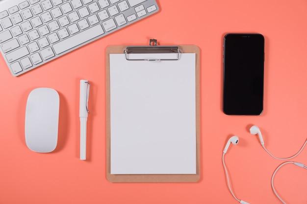 Plat liggende kalender met klembord, toetsenbord, smartphone; en potlood op levend koraal