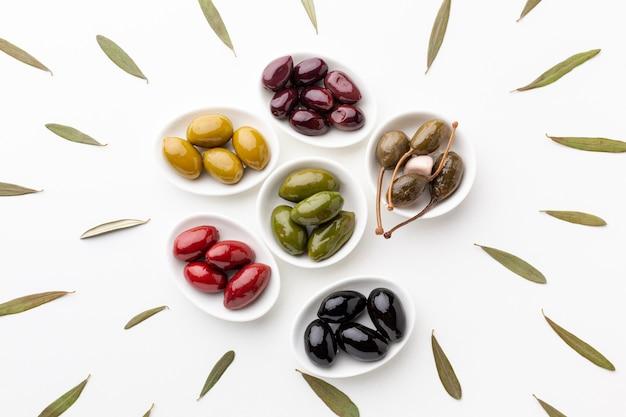 Plat liggende mix van zwart rood groen paars gele olijven en olie
