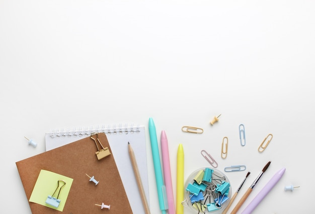 Plat liggende samenstelling van notebooks, pennen, potlood, bindmiddelen, plaknotities, paperclips en penselen.