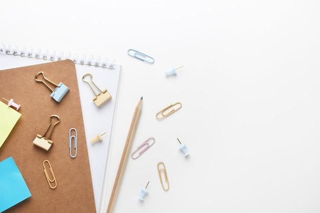 Plat liggende samenstelling van notebooks, potlood, bindmiddelen, plaknotities, paperclips. bovenaanzicht op verschillende briefpapier op het bureau.